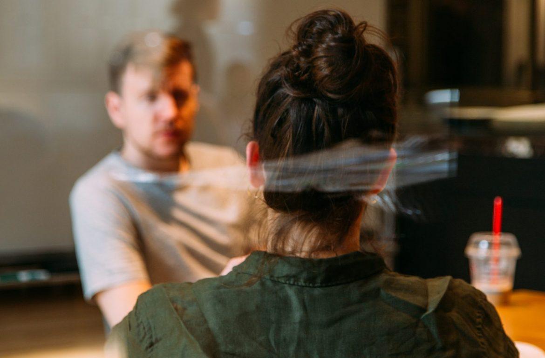 two employees talking in glass office